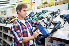 Mens die voor perforator in ijzerhandel winkelen Stock Foto