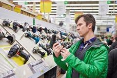 Mens die voor schroevedraaier in ijzerhandel winkelen Stock Foto