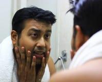 Mens die voor zijn verschijning voor een spiegelschoonheid het stileren levensstijl zorgen stock fotografie