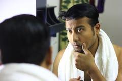 Mens die voor zijn verschijning voor een spiegelschoonheid zorgen die de lifestyleindian Aziatische mens stileren die voor zijn v royalty-vrije stock afbeeldingen