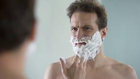 Mens die voorbereidingen treffen te scheren, voelend ongemak en tinteling op gezicht van het scheren van schuim stock video
