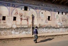 Mens die voorbij geschilderde muren in de oude Indische stijl lopen Stock Foto's