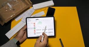 Mens die Voorraden App op recentste iPad gebruiken Pro stock foto's