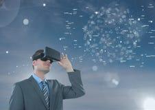 Mens die in VR-hoofdtelefoon aan een interface tegen blauwe hemel met gloed kijken Royalty-vrije Stock Afbeeldingen