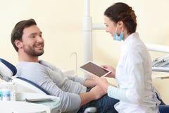 Mens die vrouwelijke tandarts bezoeken bij kliniek stock afbeelding