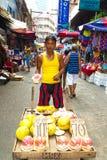 Mens die vruchten voor consumptie voorbereiden bij straatmarkt Royalty-vrije Stock Afbeelding