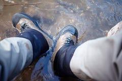 Mens die wandelingslaarzen dragen die zich in een stroom bevinden stock foto