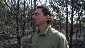 Mens die in wanhoop zijn hoed uitstellen die zich in gebrande bosaf wildfire, ecologische catastroferamp bevinden stock footage