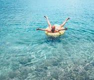 Mens die wanneer op de opblaasbare ring van de ananaspool in glashelder zeewater zwemt ontspannen Het achteloze beeld van het vak royalty-vrije stock foto