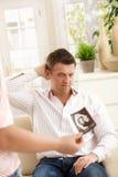 Mens die wantrouwend ultrasone klankbeeld bekijkt Royalty-vrije Stock Fotografie