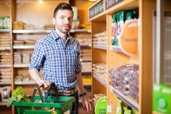 Mens die wat gezond voedsel kopen bij de kruidenierswinkelopslag Stock Foto