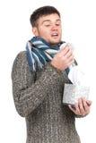 Mens die in weefsel blaast en weefsels van doos trekt Stock Fotografie