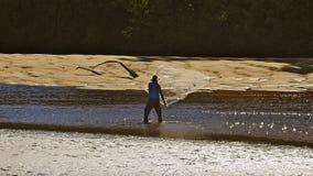 Mens die werpend werpnet in rivierwater dichtbij bank vissen Royalty-vrije Stock Afbeelding