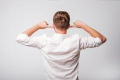 Mens die in whit overhemd met gesloten oren terug naar de camera draaien Stock Fotografie