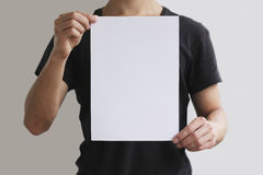 Mens die wit A4 document verticaal houden Stock Foto's