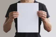 Mens die wit A4 document verticaal houden Stock Foto