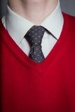 Mens die wit overhemd, rode sweater en stropdas dragen Royalty-vrije Stock Foto