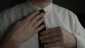 Mens die in wit overhemd zijn blauwe stropdas met beide handen aanpassen stock footage
