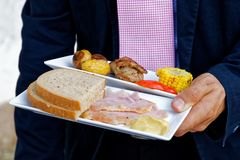 Mens die witte ceramische platen met geroosterde groenten, brood dragen Royalty-vrije Stock Foto's