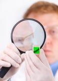 Mens die in witte laag een groene steekproef bekijkt Royalty-vrije Stock Fotografie