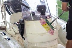 Mens die witte opblaasbare boot met borstel en het systeem van het drukwater wassen bij garage De schipdienst en seizoengebonden  stock foto
