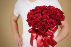 Mens die in witte t-shirt in hand rijk giftboeket van rood 21 houden Stock Fotografie
