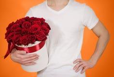 Mens die in witte t-shirt in hand rijk giftboeket van rood 21 houden Royalty-vrije Stock Foto