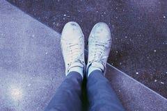 Mens die witte tennisschoenen met jeans dragen Stock Foto