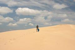 Mens die in woestijn loopt Stock Fotografie