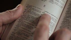 Mens die woord zoeken door vinger in Engels verklarend Woordenboek stock video