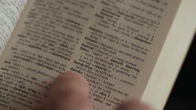 Mens die woord zoeken door vinger in Engels verklarend Woordenboek stock footage