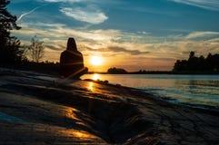 Mens die, yoga bij zonsondergang mediteren stock foto