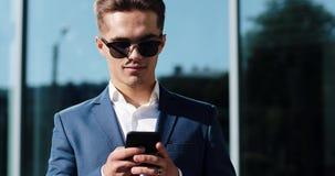 Mens die zaken app op slimme telefoon gebruiken die zich openlucht bevinden Knappe jonge zakenman die bij smartphone het glimlach stock videobeelden
