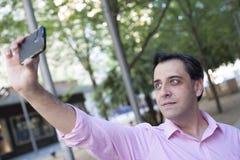 Mens die zelfportret met mobiele telefoon nemen Stock Foto's