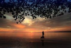 Mens die zich bij een zonsondergang bevindt Stock Fotografie