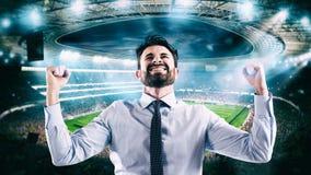 Mens die zich bij het stadion voor het winnen van een rijke voetbalweddenschap verheugt stock foto's