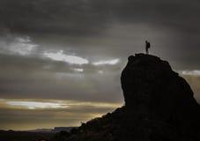 Mens die zich bovenop een berg bevinden Stock Afbeeldingen