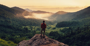 Mens die zich bovenop klip bij zonsondergang bevinden Stock Foto