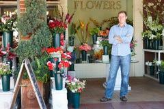Mens die zich buiten bloemist bevindt Stock Foto's