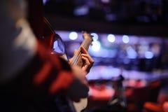 Mens die zich in de nachtclub bevinden met een gitaar in zijn handen Royalty-vrije Stock Afbeelding