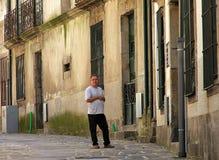 Mens die zich dichtbij de deur op één of andere smalle straat van Porto bevinden stock fotografie