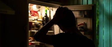 Mens die zich dichtbij de geopende koelkast bevinden om wat voedsel bij nacht F thuis te plukken stock fotografie