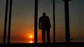 Mens die zich dichtbij glasdeuren van het huis bij zonsondergang bevinden stock video