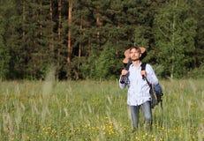 Mens die zich dichtbij pijnboomhout bevinden met akoestische gitaar en rugzak Het concept van de de zomerreis Royalty-vrije Stock Fotografie