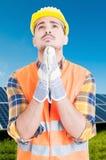 Mens die zich door zonnepaneel en te bidden bevinden Stock Afbeelding