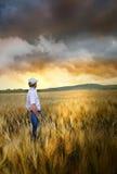 Mens die zich in een wheatfield bevindt stock foto