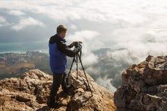 Mens die zich met een driepoot en een camera op een hoge bergpiek bevinden boven wolken, stad en overzees Professionele fotograaf Stock Afbeeldingen