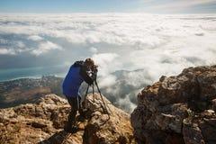 Mens die zich met een driepoot en een camera op een hoge bergpiek bevinden boven wolken, stad en overzees Professionele fotograaf Stock Foto's