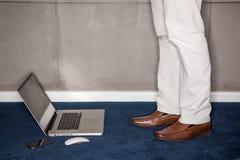 Mens die zich met laptop in bureau bevindt royalty-vrije stock foto
