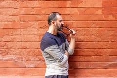 Mens die zich met sommige glazen in zijn mond bevinden royalty-vrije stock foto's